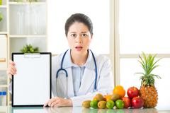 Doctor nutritionist with fruits and holding blank clipboard fell fear - stock photo