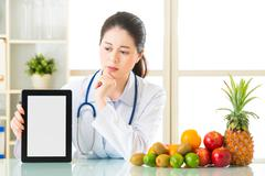Doctor nutritionist with fruits and holding digital tablet fell doubt Stock Photos