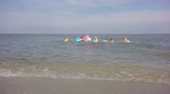 Four young children with her mother playing on the sea. - stock footage