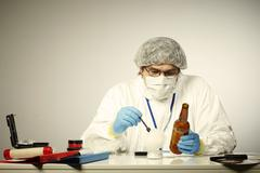 Criminologist exploring fingerprints on bottle - stock photo