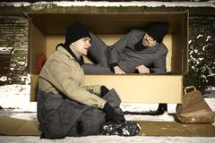 Two ugly men sharing paper box in winter city park - stock photo