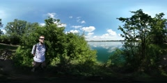 360Vr Video Man in Sun Glasses on Lake Bank Bicycle is Parked at the Bushes Stock Footage