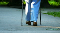 Slow motion. Old age woman with sticks for walking go in park.  Stock Footage
