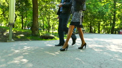 Slow motion. Female and male silhouettes in summer city park   Stock Footage