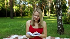 Girl in the park reading a book. Girl has a rest with a book on nature. Stock Footage