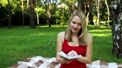 Girl in the park reading a book. Activities in the park and pleasant hobby. - stock footage