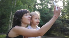 Cute family mother with child daughter taking selfie smart phone photo on nature - stock footage