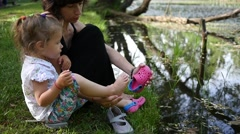 Mother shoe a crocs footwear to child daughter on family weekend picnic by water - stock footage