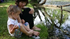 Family weekend by a water lake sitting mother and little cute child daughter Stock Footage