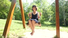 Young pretty woman is happy and have fun swaying on a swing in a nature park Stock Footage