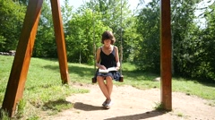 Young woman sway on a swing in a nature park reading leafing a real paper book Stock Footage