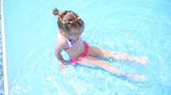 Little kid girl swim in a swimming pool clear water on summer resort - stock footage