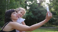 Photo selfie family mother and little kid daughter hugging kissing shooting Stock Footage
