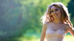 Young sexy blonde girl in pink elegant dress standing in the woods Stock Footage