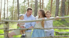 Happy young caucasian children communicating and laughting with parents on park. Stock Footage