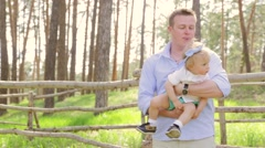 Dad holding kissing his sweet daughter baby with a bow on her head, baby laughs - stock footage