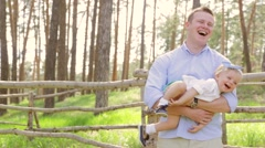 Dad holding his sweet daughter baby with a bow on her head, baby laughs - stock footage