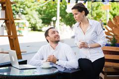 Business Team man and woman at Cafe having a conversation using laptop. Working Stock Photos