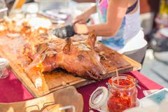 Roasted suckling pig served on food stall. Stock Photos