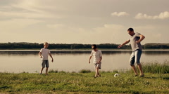 Father and two son playing football on the beach at the day time. Concept of - stock footage