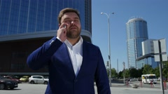 Business man in blue suit talking on the phone on the street. 4k Stock Footage