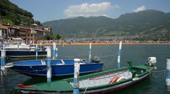 Moored boats and people walking on the floating Piers on Lake Iseo Italy Stock Footage