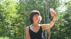 Cute brunette woman take selfie photo via smart phone rest on nature park Stock Footage