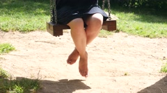 Young woman female legs during swaying sitting on swing on nature park Stock Footage