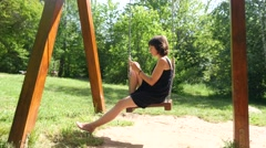 Brunette woman type smart phone messenger swaying on swing in nature park - stock footage