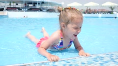 Cute little child girl have fun swim in swimming pool water at summer resort - stock footage