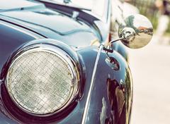Shiny blue vintage car, detail view of the headlight, photo filter Stock Photos