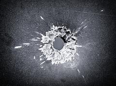 Bullet hole in the metal plate, black and white photo Stock Photos