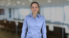 Confident professional female with hands on hips in an office Stock Footage