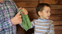 The father wipes his son's hands from smeared paint Stock Footage
