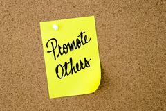 Promote Others written on yellow paper note Stock Photos