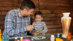 Father and son paint colors ceramic vase Stock Footage