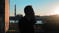 Silhouette of businessman smoking cigarette - stock footage