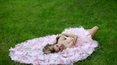 Young sexy blonde girl in pink elegant dress lying on the green lawn Stock Footage