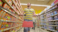 Guy with full supermarket trolley approaching camera and smiling happily, young Stock Footage