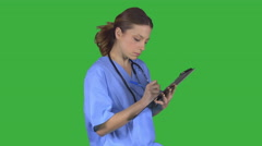 Nurse takes notes on clipboard (Green Key) - stock footage