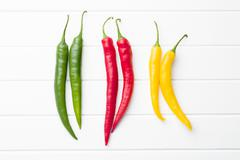 Different colors chili peppers. Stock Photos