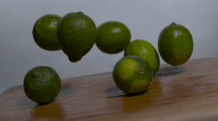 Limes falling in slow motion onto a cutting board - moving barrel roll shot - stock footage