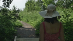 Young girl in hat and long dress comes along the path, fps96 Stock Footage