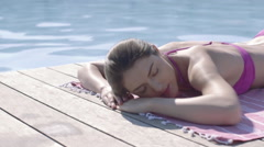 Attractive woman sunbathing by pool Stock Footage