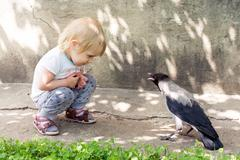 Girl playing with a hooded crow Kuvituskuvat