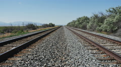 Zoom in-Parallel railroad tracks merge to distant vanishing point Stock Footage