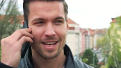 Young handsome man stands and talks to somebody on phone in park - closeup Stock Footage