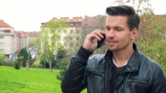 Young handsome man stands and talks to somebody on phone in park Stock Footage