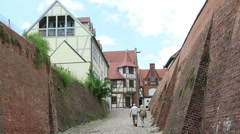 Couple walking along the street at town wall of Tangermuende Stock Footage