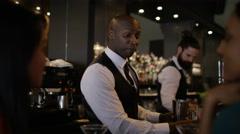 4K Smiling bartender prepares & serves fresh cocktails for female customers Stock Footage